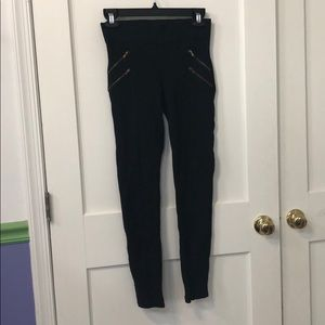 Black pants with zipper detail.